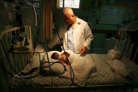 Docotr treats baby in Gaza hospital (image from electronicintifada.net)