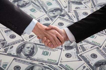 white men in suits shaking hands over a pile of US cash
