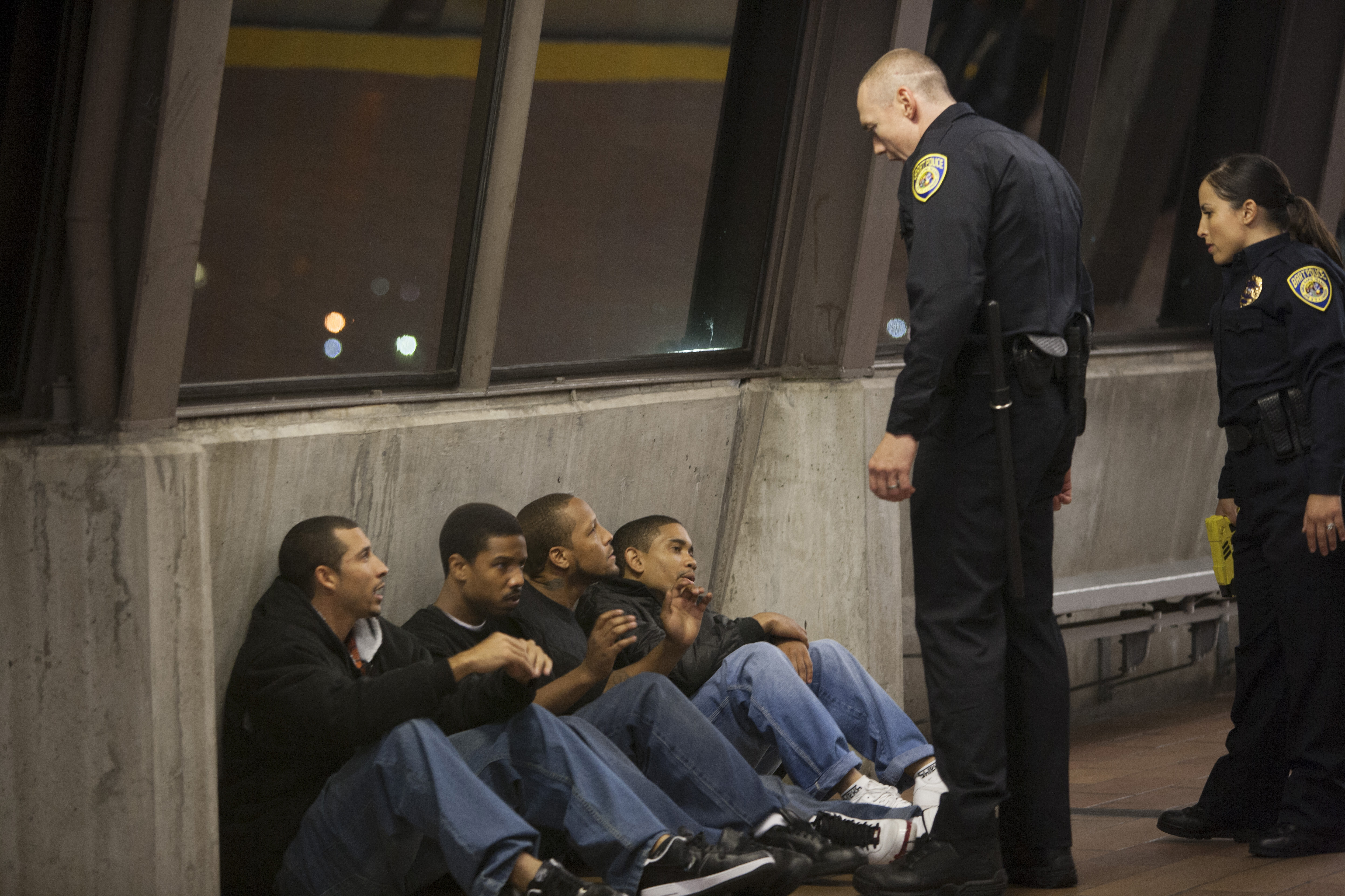 White cop leaning over young brown men in movie Fruitvale Station
