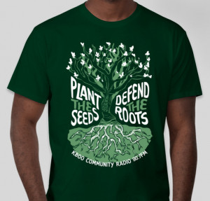 "Green t-shirt worn by model. Shirt has an illustration of a tree with text surrounding the tree reading ""Plant the Seeds, Defend the Roots"""
