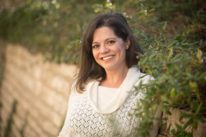 Photograph of poet Traci Brimhall, a smiling woman with dark hair, wearing a white sweater