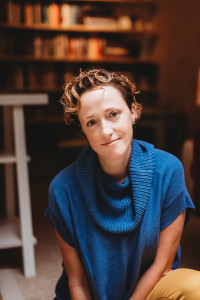 Photo of a woman with short, curly hair wearing a blue sweater