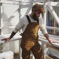 Farmer Brian Hulsey, wearing overalls and a sweater, looks serenely towards an empty shelf in an all white greenhouse.